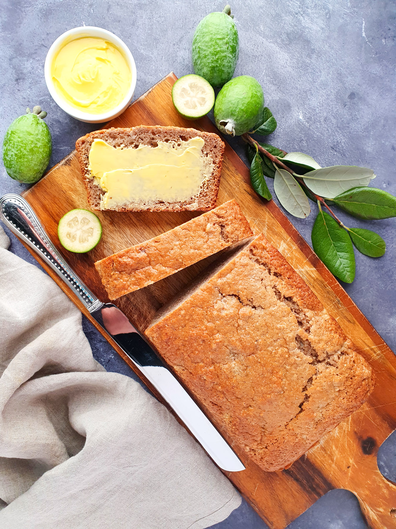Sliced feijoa loaf on a chopping board, with one buttered slice, fresh feijoas and leaves and a butter knife.