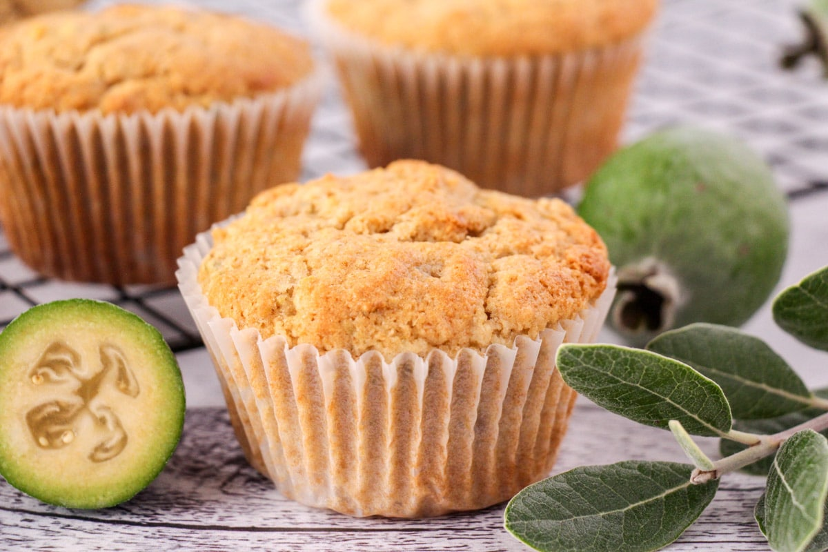 Feijoa muffins with fresh feijoas and feijoa leaves, with extra muffins on a cooling rack in the background.