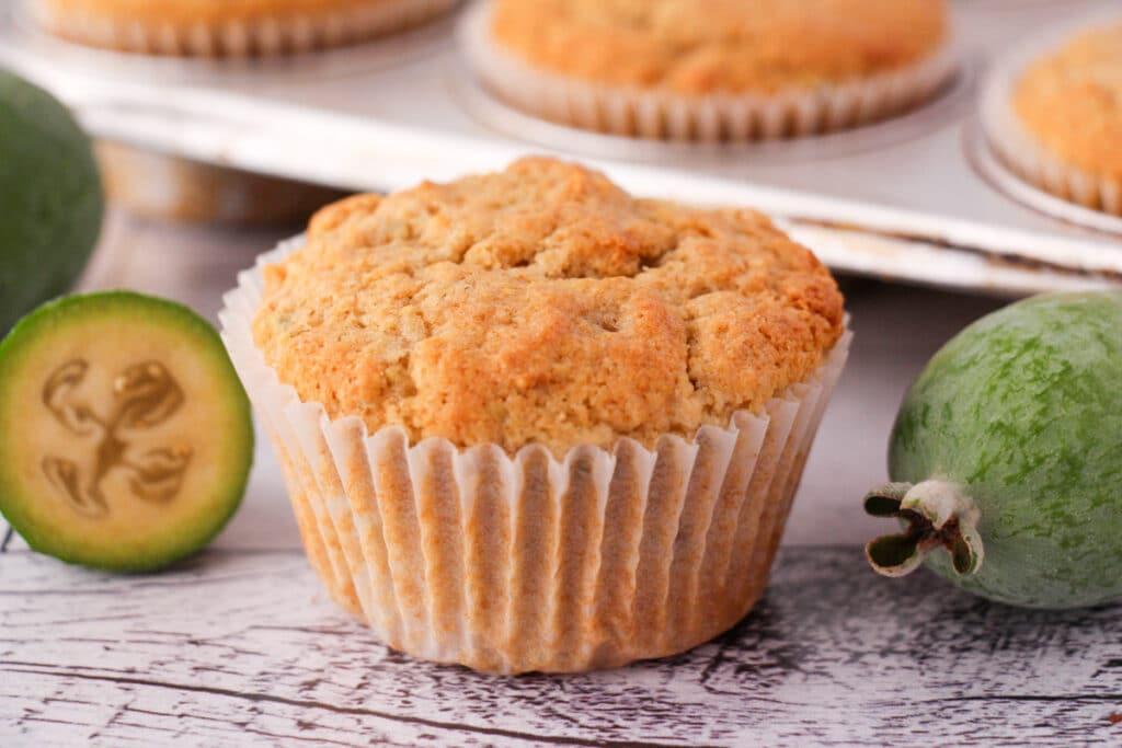 Feijoa muffins with fresh feijoas and feijoa leaves, with extra muffins in muffins tins in the background.