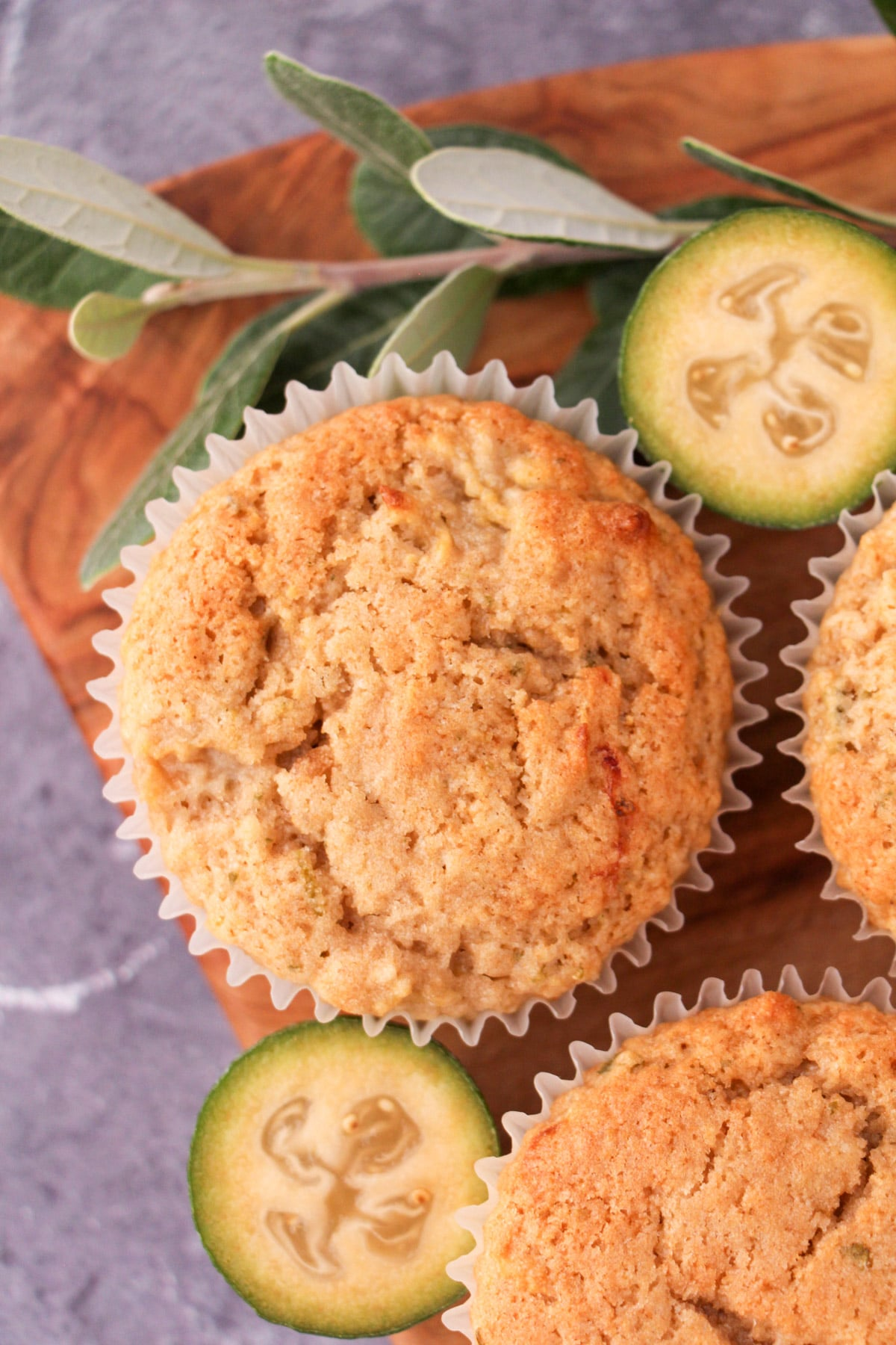 Feijoa muffins on a board with fresh feijoas and feijoa leaves.