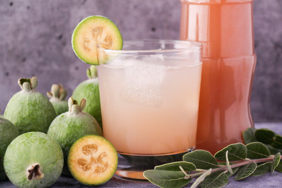 Glass of made up feijoa syrup with ice and fresh feijoa garnish, with bottle of feijoa syrup and fresh feijoas and leaves.