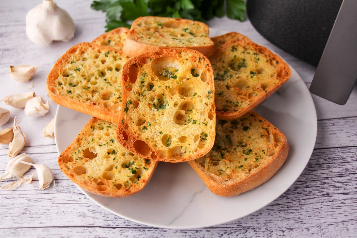 Stack of air fryer garlic bread on a plate, with air fryer basket and fresh garlic cloves to the sides.