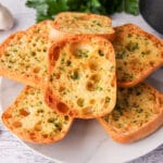 Close up of stack of air fryer garlic bread on a plate, with air fryer basket and fresh garlic cloves to the sides.