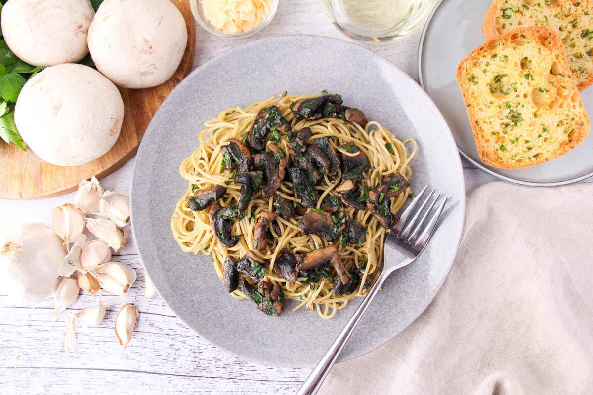 Mushroom aglio olio on a plate with a fork, with garlic bread, fresh garlic, mushrooms and parsley, a glass of white wine and shaved parmesan around the edges.