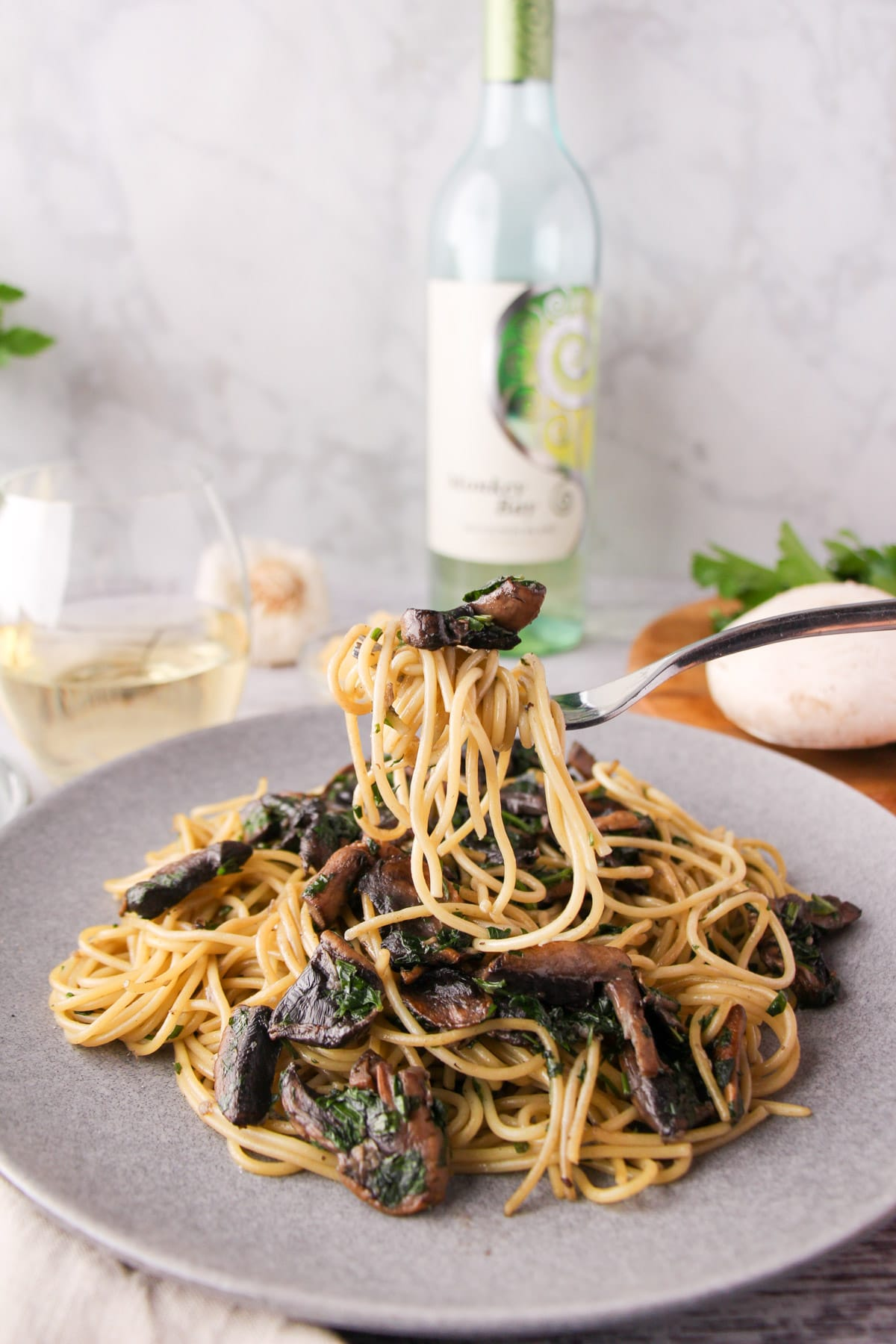 Fork of mushroom aglio olio held over a plate of pasta, with fresh mushrooms, parsley, garlic and a glass and bottle of white wine the background.