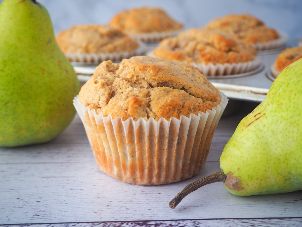 Pear muffin with fresh pears and tray of muffins in the background.