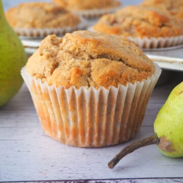 Close up pear muffin with fresh pears and tray of muffins in the background.
