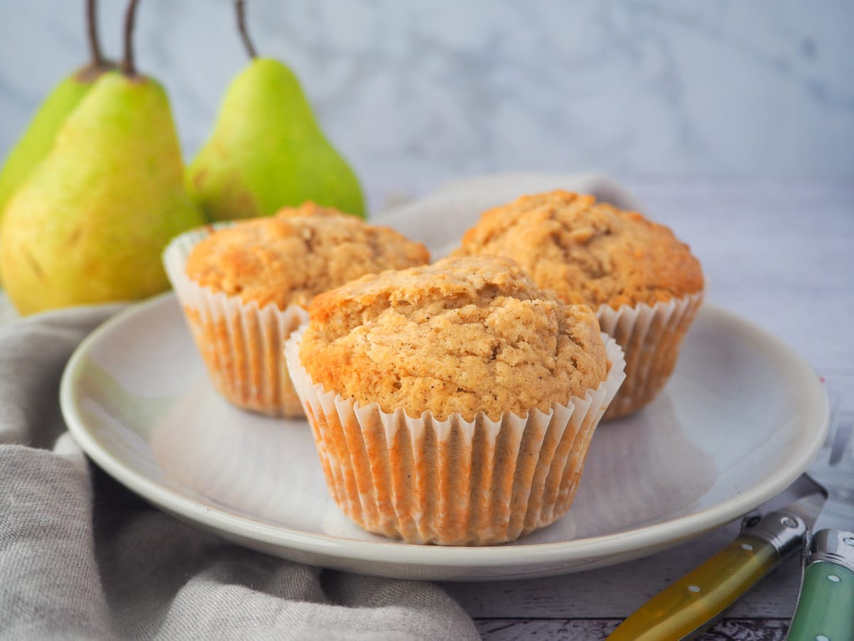 Plate of three pear muffins, with forks and fresh pears in the background.