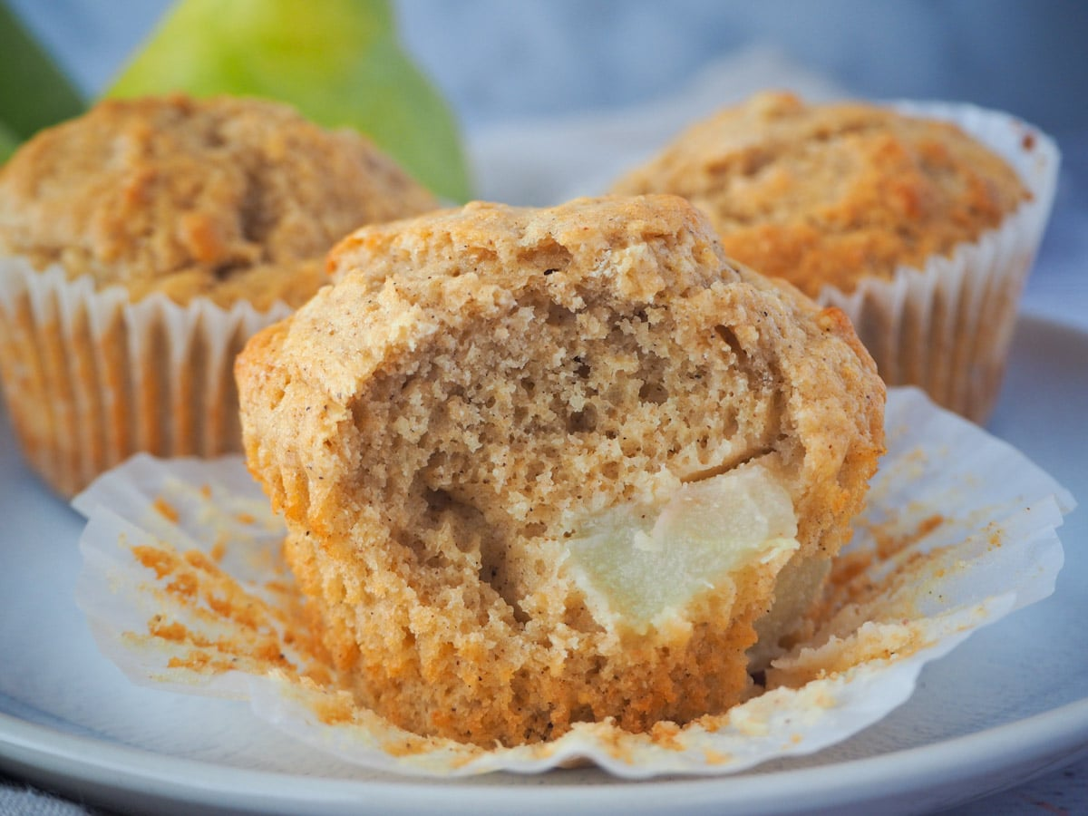 Pear muffin with a piece taken out, with more muffins and fresh pears in the background.