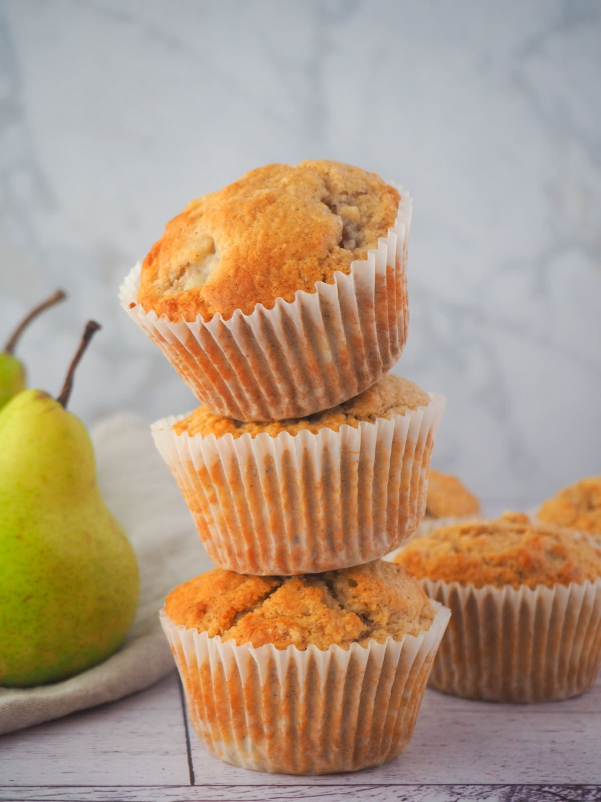 Stack of pear muffins with fresh pears.