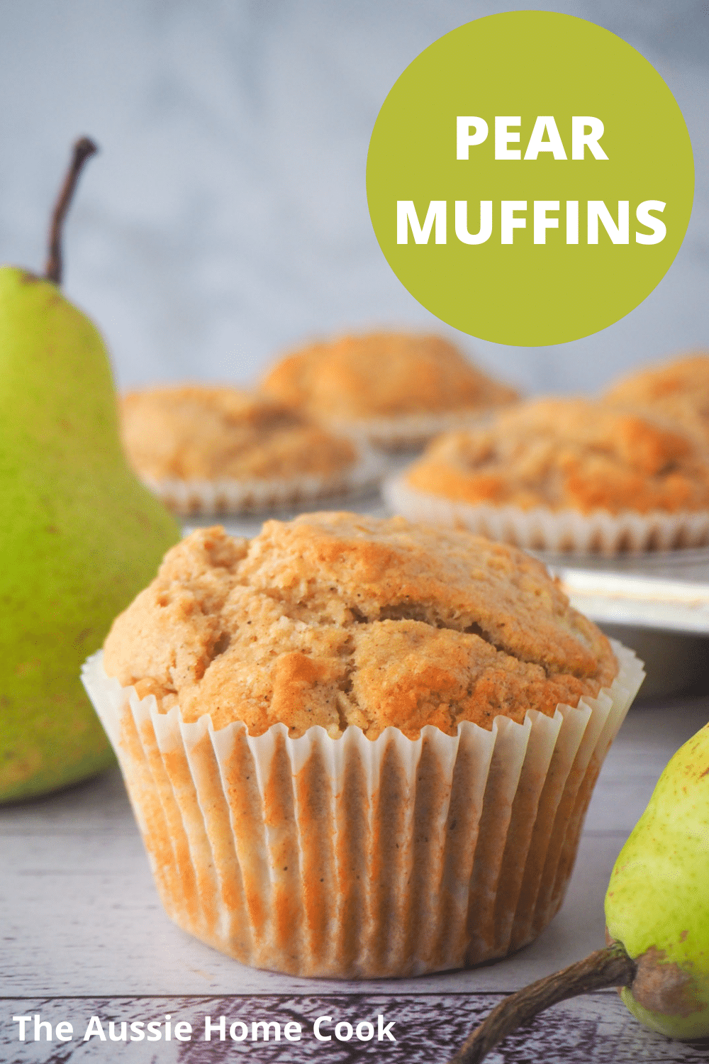 Pear muffin with fresh pears and tray of muffins in the background, and text overlay, pear muffins, the aussie home cook..