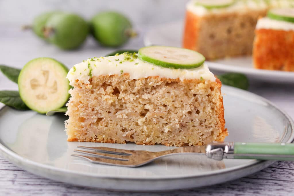 slice of feijoa cake on a plate with a cake fork, the rest of the cake and fresh feijoas and leaves in the background.