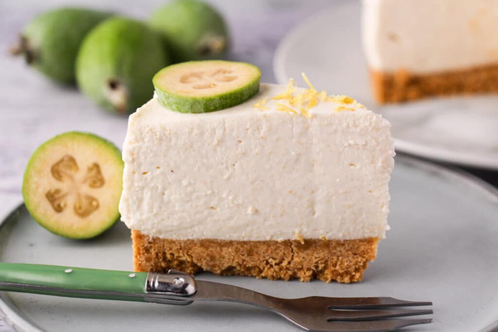 Feijoa cheesecake with slice taking out, silver serving ware and fresh feijoas and feijoa leaves in the background.
