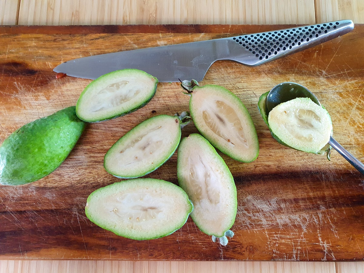 Slicing open feijoas and scooping out flesh.