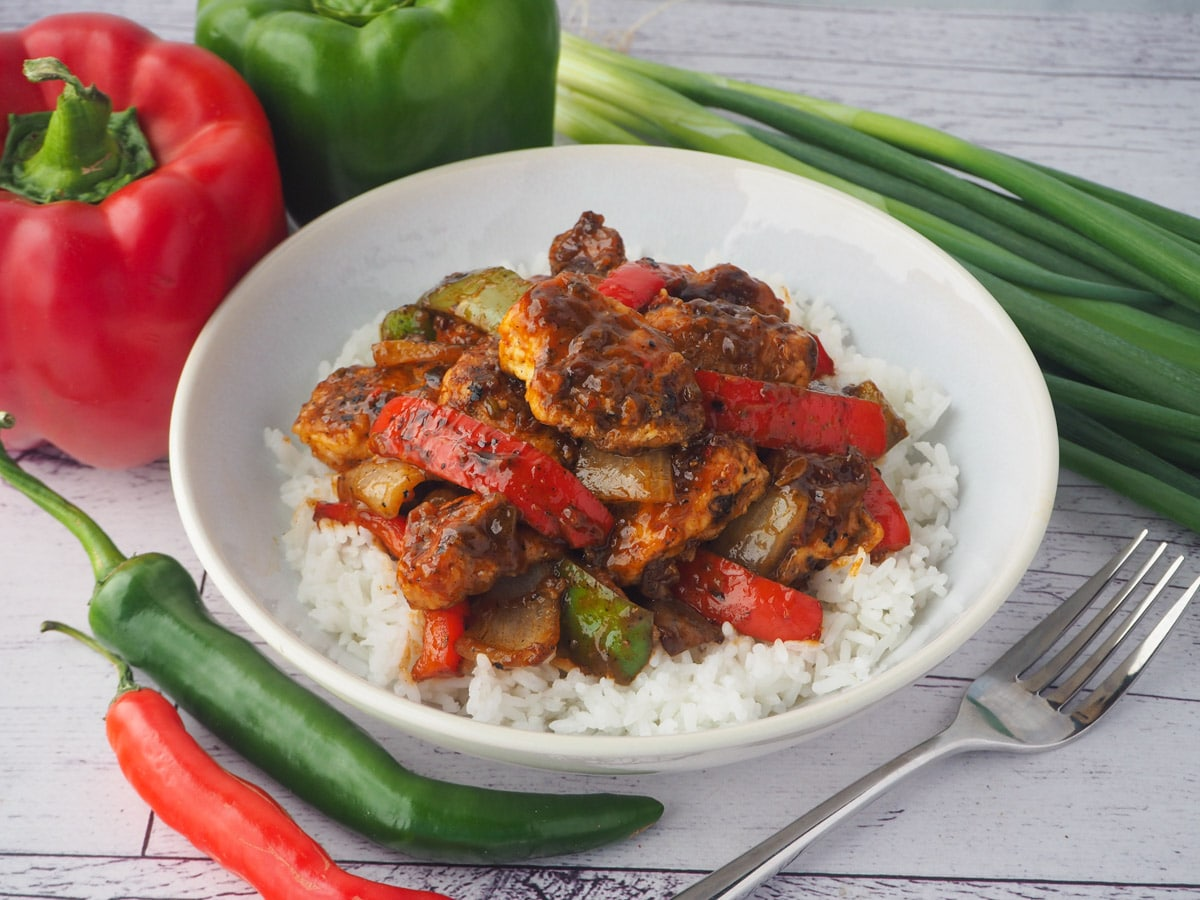Bowl of chicken on rice with fork and capsicums, spring onions and chilli on the side.