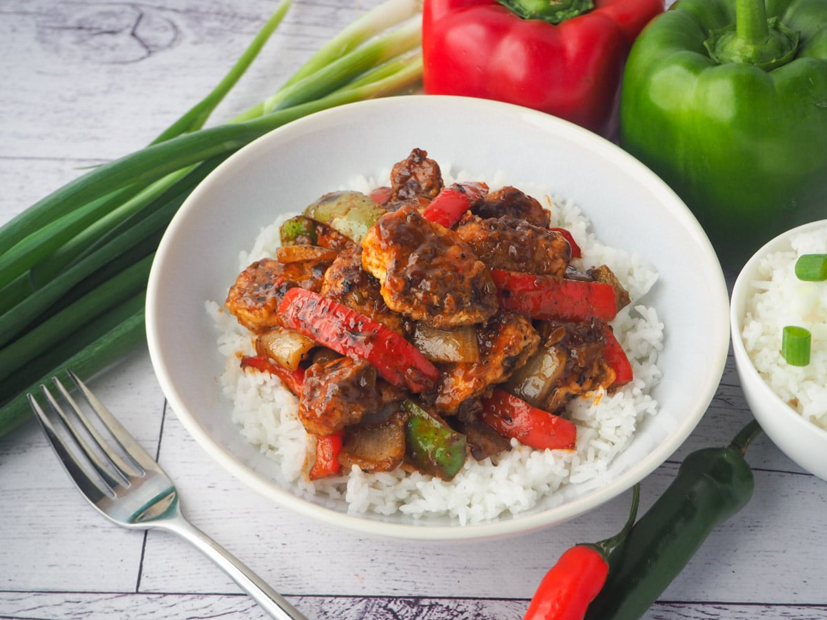 Bowl of chicken on rice with fork, bowl of rice, capsicums, spring onions and chilli on the side.