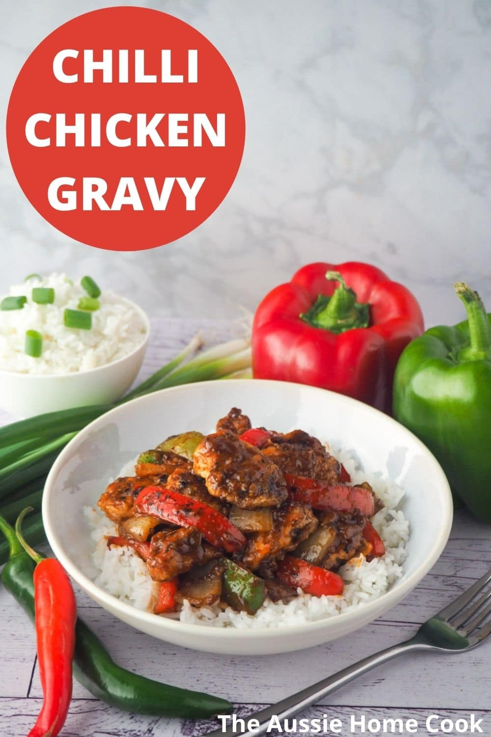 Bowl of chicken on rice with fork and capsicums, spring onions and chilli on the side with text overlay, chilli chicken gravy and The Aussie Home Cook.