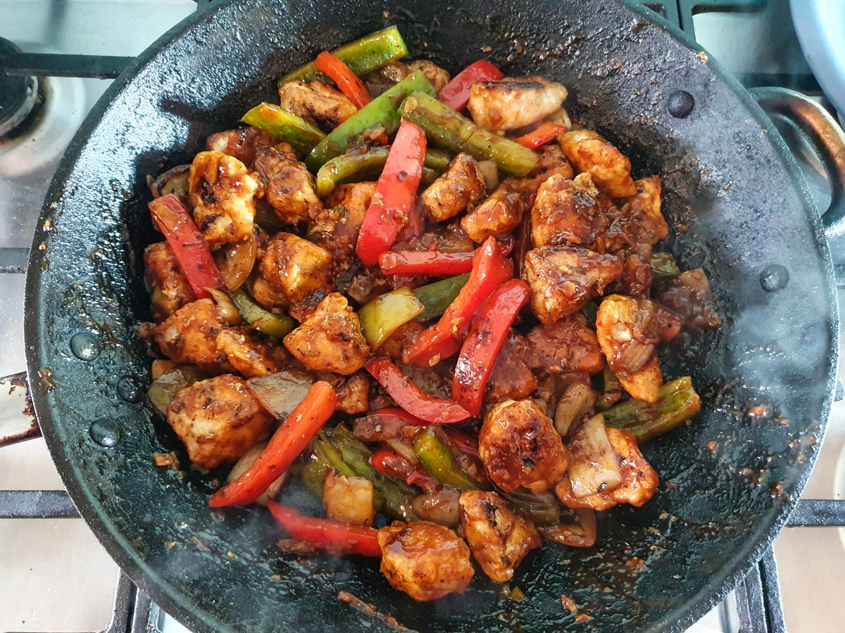Stirring to coat chicken and vegies in sauce.