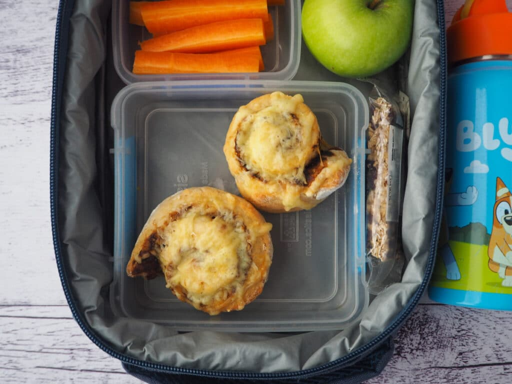 Scrolls in a lunchbox with carrot sticks, apple, muslie bar and drink bottle.