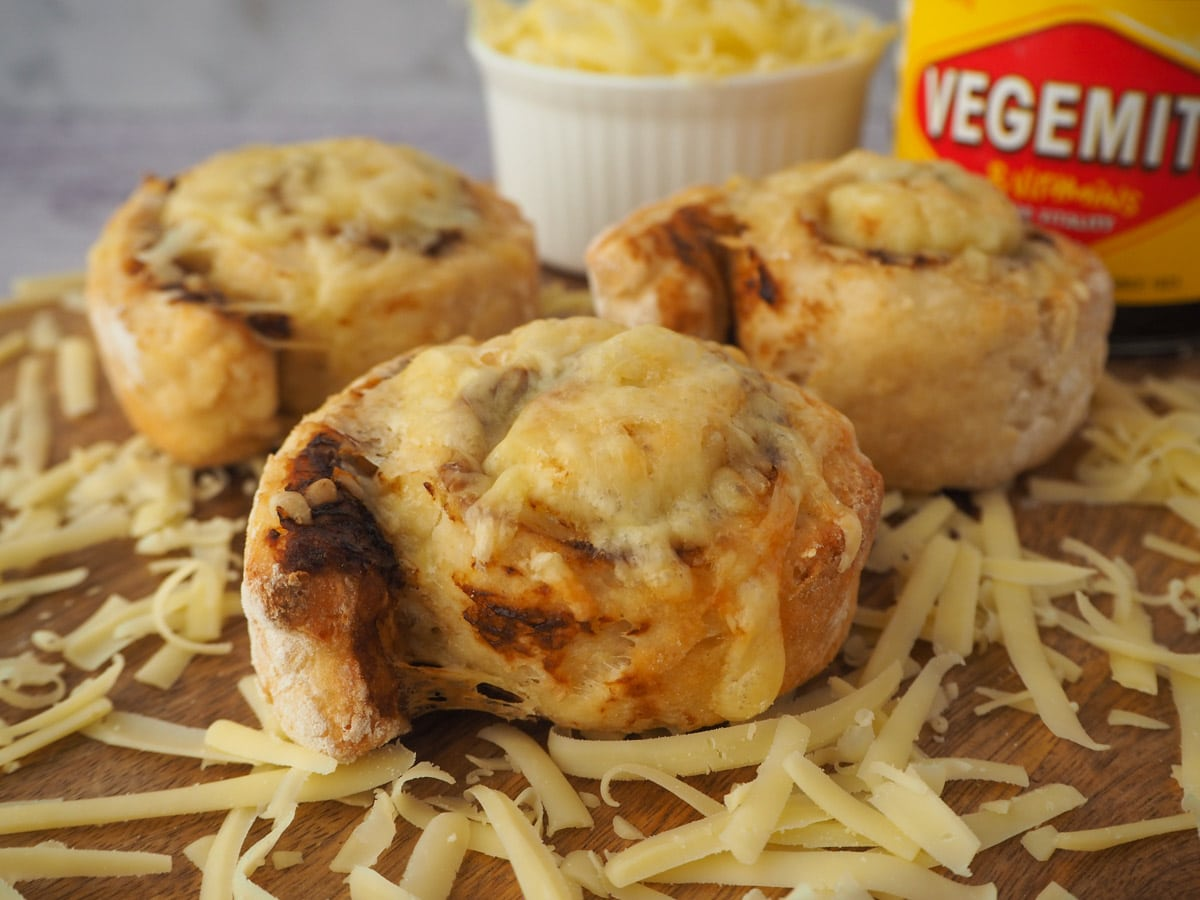 Scrolls on a board surrounded by grated cheese, with bowl of cheese and jar of vegemite in the background.