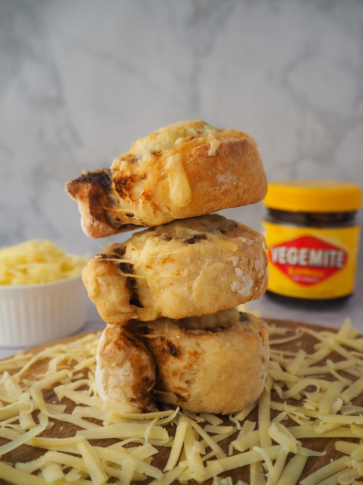 Stack of scrolls surrounded by grated cheese, with bowl of grated cheese and jar of vegemite in the background.