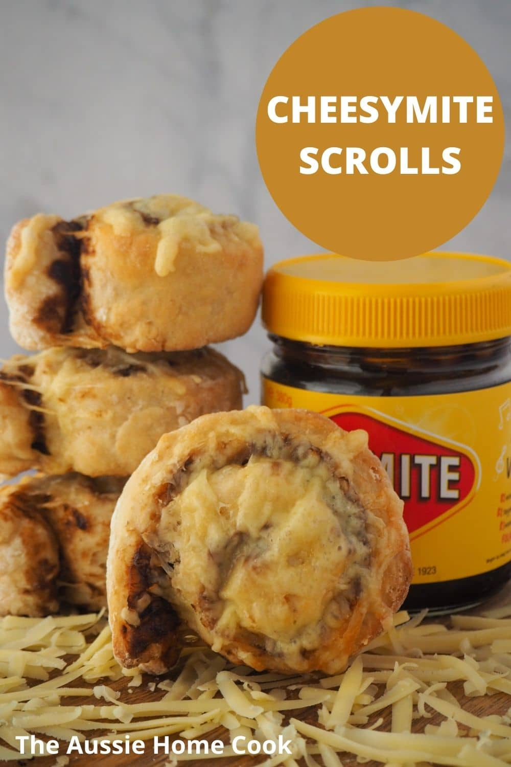 Scroll with stack of scrolls and jar of vegemite at the back, grated cheese and the front and text overlay, cheesymite scrolls and The Aussie Home Cook.