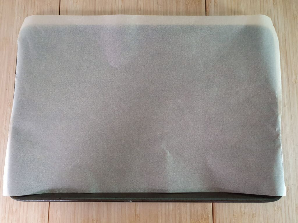 Lining a tray with baking paper.