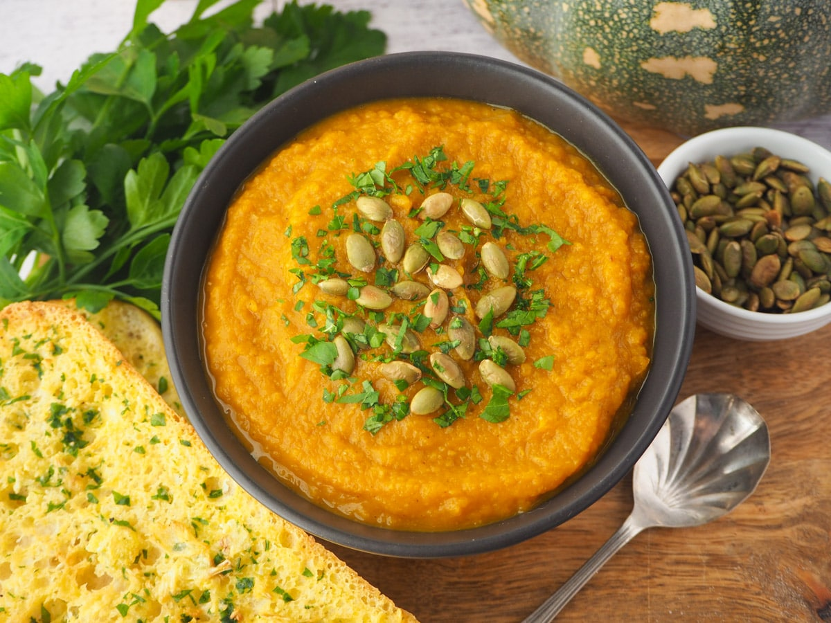 Soup with pumpkin seed and parsley garnish, with garlic bread, spoon and toasted pumpkin seeds on the side.