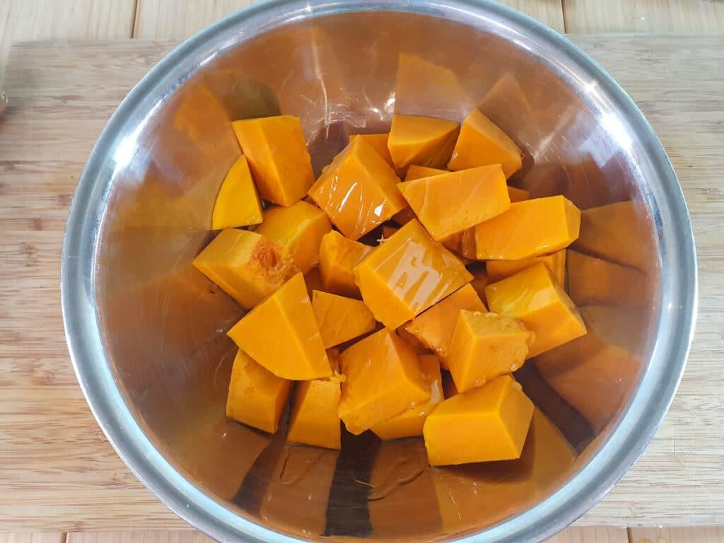 Coating the pumpkin chunks in olive oil.
