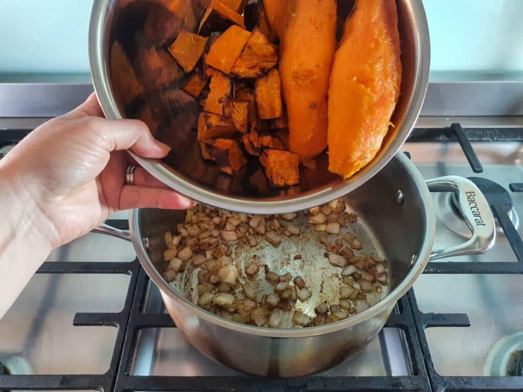 Adding the roast pumpkin and sweet potato to the stock pot.